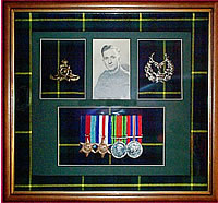 Framed medal display including photograph, medals and badges